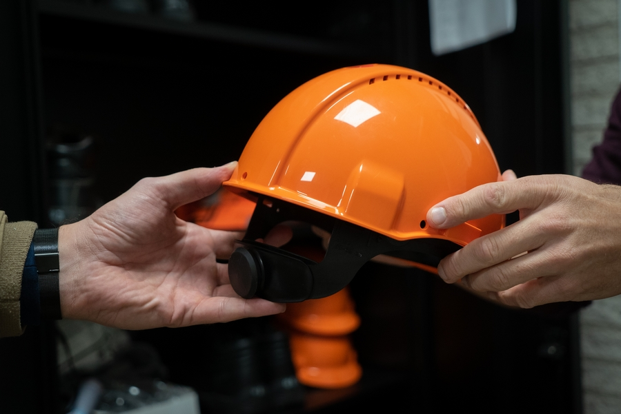 industry worker handing over a safety helmet